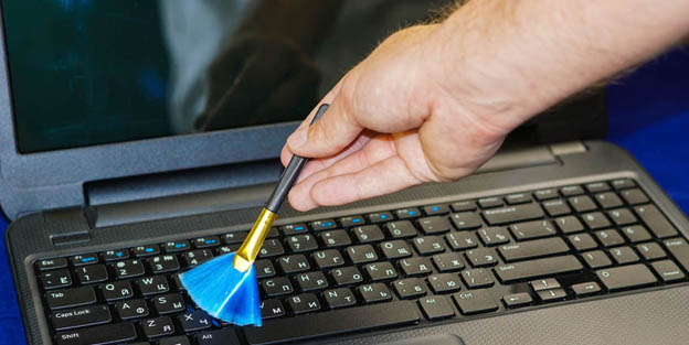 Computer cleaning brush on a laptop