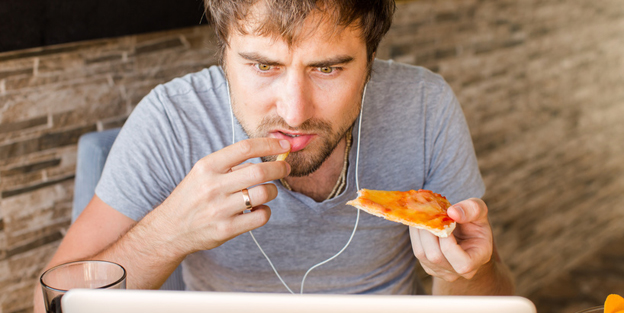 Man working at the computer and eating fast food. Unhealthy Life