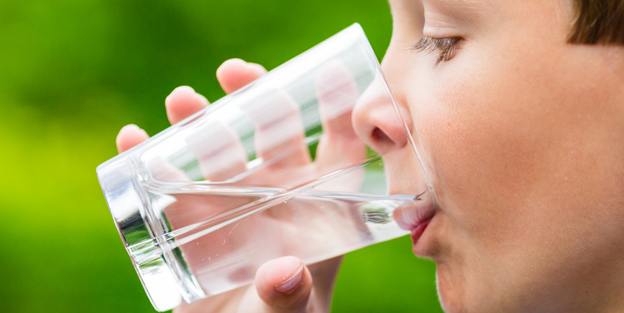 Child drinking glass of fresh water