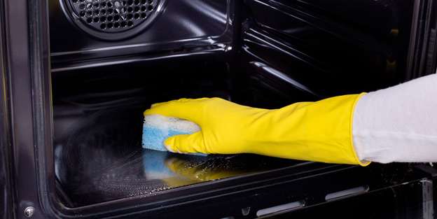 Woman cleaning oven